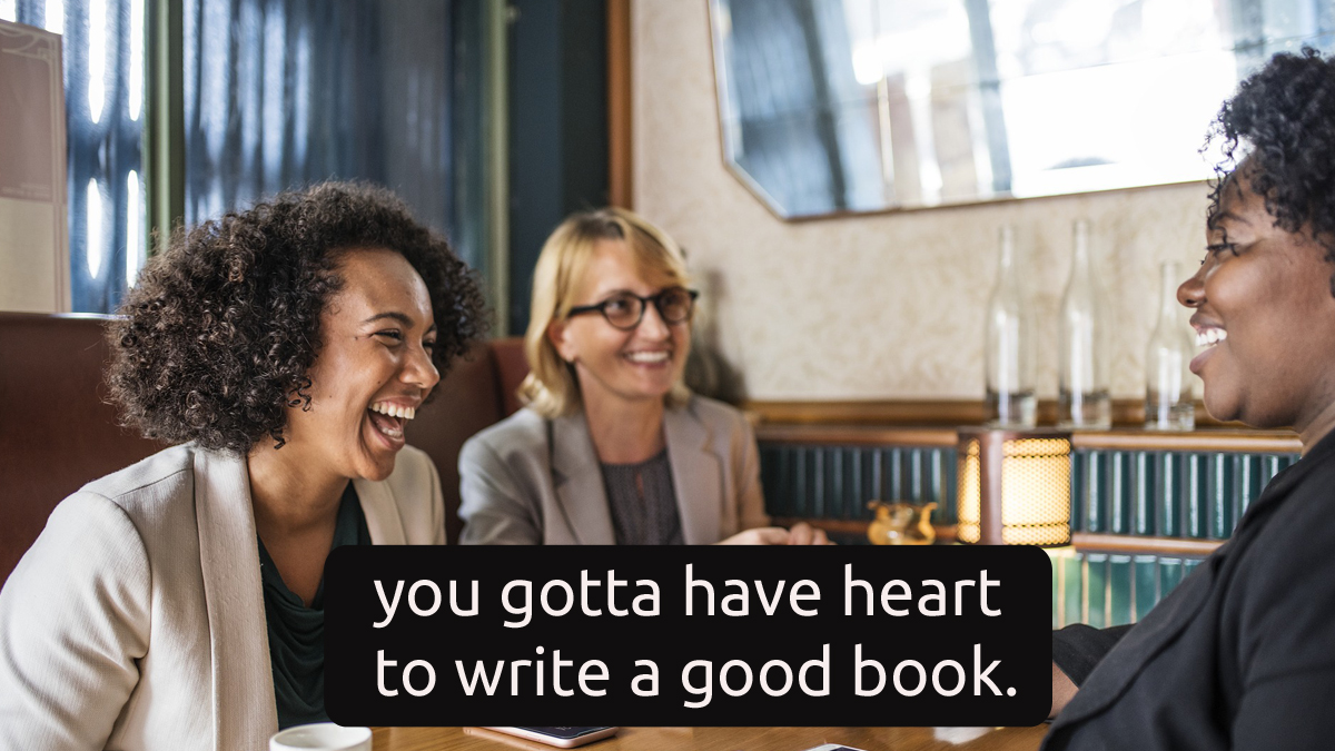 """Two women of color at a restaurant table, nearly doubled over in laughter, with words saying, """"It takes heart to write a good book."""""""